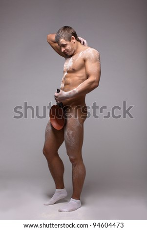 beautiful naked man athlete with a frying pan and flour