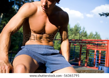 beautiful naked muscular body of a young man on the street. Unrecognizable - stock photo