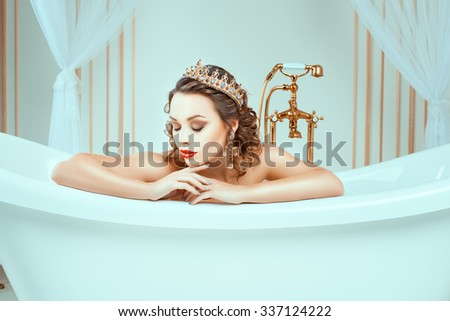 Beautiful naked young woman sitting in expensive jewelry bath. In the face of a bright fashion make-up on her head a crown. - stock photo
