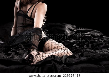 Beautiful naked young woman with blond hair sitting in black bed - stock photo