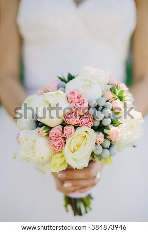 Beautiful natural and simple wedding bouquet in bride's hand - stock photo