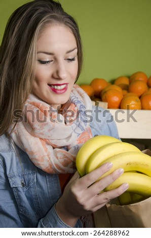 Beautiful natural brunette buying bananas and smiling - stock photo