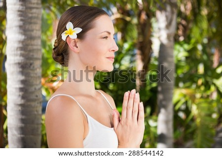Beautiful natural brunette doing yoga on green background - stock photo