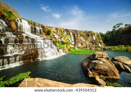 Beautiful natural cascading waterfall with crystal clear water in Vietnam. Summer sunny landscape. Blue sky in background. The Pongour waterfall (PonGour) is a popular tourist destination of Asia. - stock photo