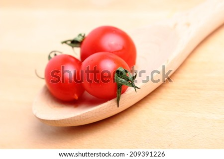 Beautiful natural cherry tomatoes on a wooden spoon