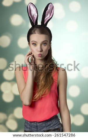 Beautiful, natural, gorgeous, blonde woman with funny, fluffy rabbit ears on the head. She has got nice make up and outfit. - stock photo