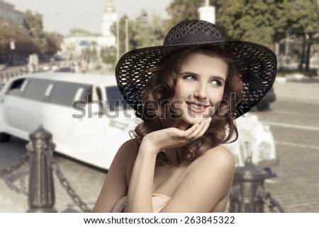 Beautiful, natural, gorgeous brunette woman with nice curly hairstyle and colorful makeup. She is wearing summer hat she is smiling. - stock photo