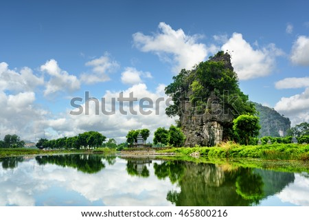 Beautiful natural karst tower reflected in water of the Ngo Dong River at the Tam Coc portion, Ninh Binh Province, Vietnam. The Tam Coc is a popular tourist attraction in Asia.
