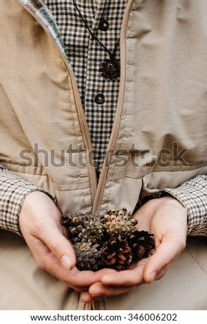 beautiful natural pine cones in hands on a background of forest, protect the environment