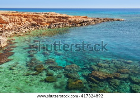 Beautiful natural rock arch near of Ayia Napa, Cavo Greco and Protaras on Cyprus island, Mediterranean Sea. View near of Legendary bridge lovers. Amazing blue green sea and sunny day. - stock photo