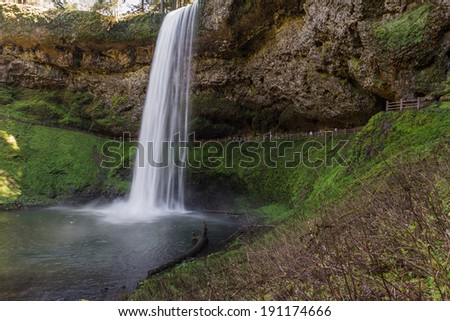 beautiful natural scene of silver lake falls in Oregon with blurred people in the path behind them - stock photo