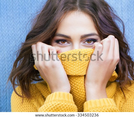 Beautiful natural young shy brunette woman with smiling eyes wearing knitted sweater  - stock photo