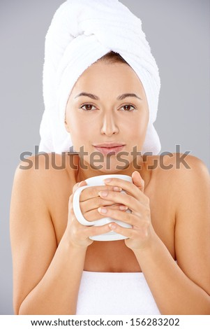 Beautiful natural young woman wrapped in fresh white towels enjoying a mug of hot coffee at a spa holding it cupped in her hands - stock photo