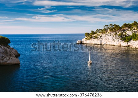 Beautiful nature of Calanques on the azure coast of France. Calanques - a deep bay surrounded by high cliffs. Yacht boat leaves from bay to open sea. - stock photo