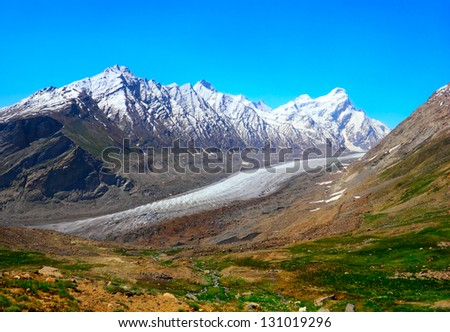 Beautiful nature scenery with melting glacier in rugged rocks covered with snow and field against the background of bright blue sky in Himalaya mountains, Ladakh range, Jammu & Kashmir, Northern India - stock photo
