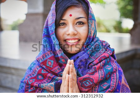 beautiful nepalese woman saying and performing namaste gesture - stock photo