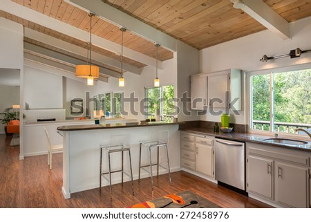Beautiful New kitchen in mid century home with open floor plan, cabinets, cherry wooden floor and wooden ceiling. Kitchen in white with granite counter tops with stainless steel oven and stove. - stock photo