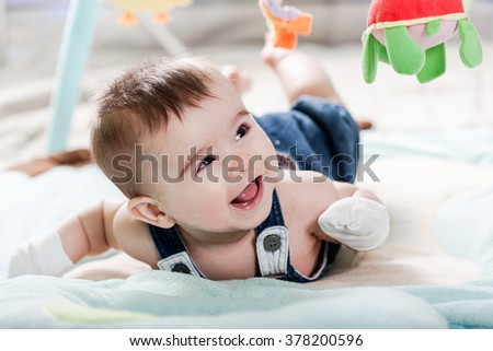 Beautiful newborn baby girl playing on the colorful rug.