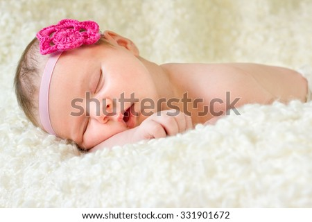 Beautiful newborn baby girl sleeping on a blanket - stock photo