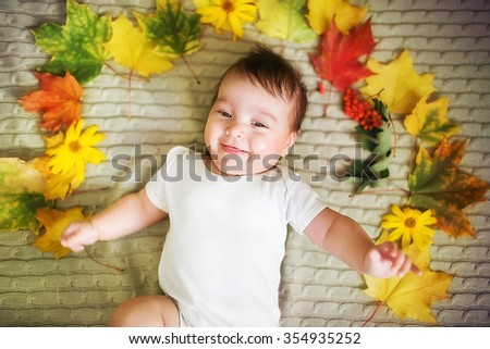 Beautiful newborn baby lies with maple leaves. Autumn concept - stock photo