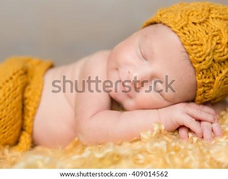 beautiful newborn baby lying on woolen blanket in wicker basket - stock photo