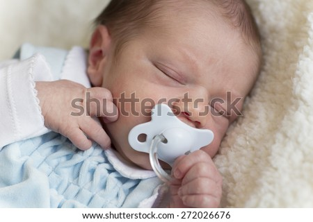 Beautiful newborn baby with blue pacifier, lying on a blanket and sleeping peacefully - stock photo