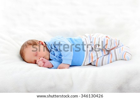 beautiful newborn sleeping on bed