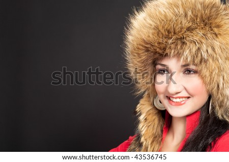 beautiful nice dark haired girl in winter fur hat with nice smile isolated on black background