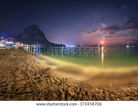 Beautiful night landscape at the seashore with yellow sand, mountains and lunar path. Panoramic view. Vacations on the beach at the sea. Travel background
