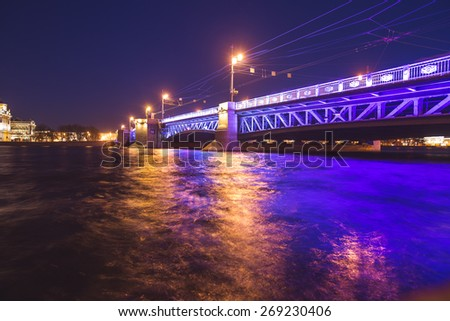 Beautiful night panoramic picture of Saint-Petersburg, Russia, with most famous Palace Bridge with beautiful illumination, palace embankment, with Saint Isaac's Cathedral and Neva river  - stock photo