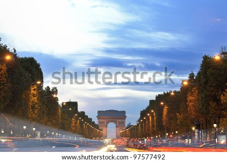 Beautiful night view with car traffic and rush at eavning of the Arc de Triomphe, Paris, France. - stock photo