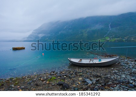 Beautiful norwegian cold morning landscape with boat, lake and mountains - stock photo