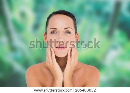 Beautiful nude brunette posing with hands on face on blue and green background