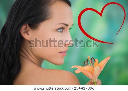 Beautiful nude brunette smelling lily against heart - stock photo