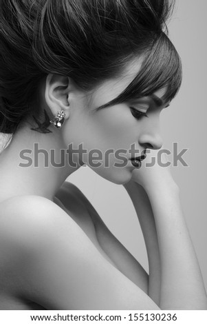 beautiful nude woman with perfect skin, makeup and jewelry - stock photo