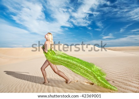 Beautiful nude woman with scarf in desert