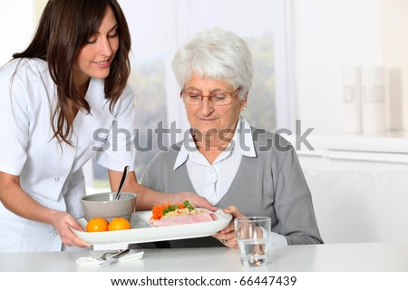 Beautiful nurse bringing meal tray to old woman at nursing home - stock photo