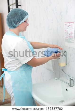 Beautiful nurse, washes his hands before the procedure,wiped his hands dry. midwife washes his hands before delivery. surgical hand washing