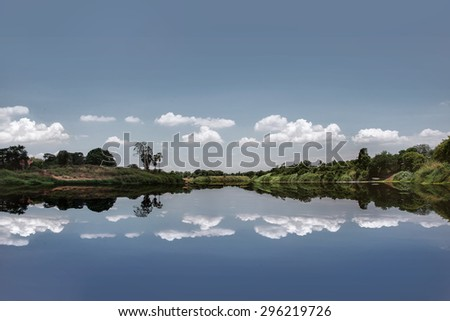 Beautiful of nature - The photo of pastel blue minimal picture with reflection of trees , cloudy sky like a mirror on the water  from countryside of thailand in square - stock photo