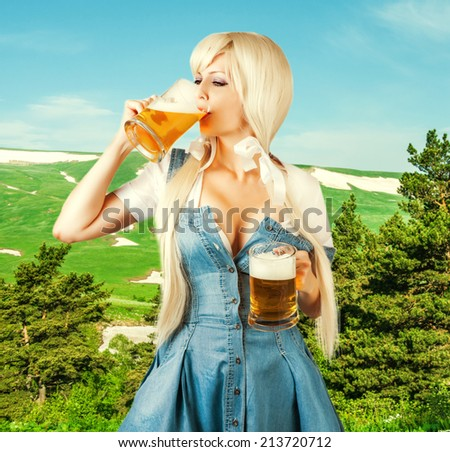 Beautiful oktoberfest young sexy woman wearing a dirndl with two froth beer mugs drink beer outdoor on green alpine meadow