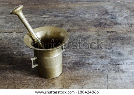Beautiful old bronze mortar with pestle on wootden table