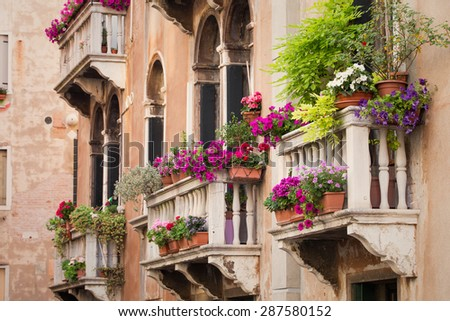 Beautiful old building balconies with colorful flowers - stock photo