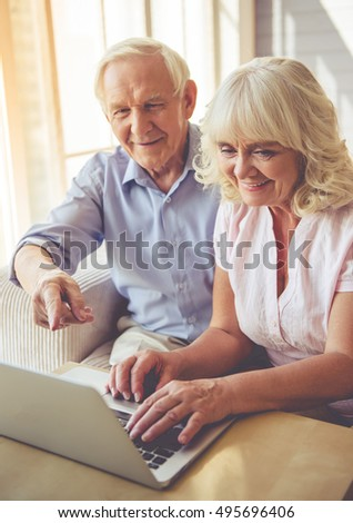 Beautiful old couple is using a laptop and smiling while sitting on couch at home