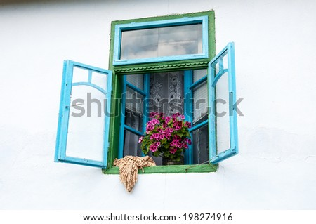 Beautiful old-fashioned window with flowers and scarf
