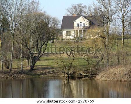 Beautiful old house in countryside behind lake at spring - stock photo