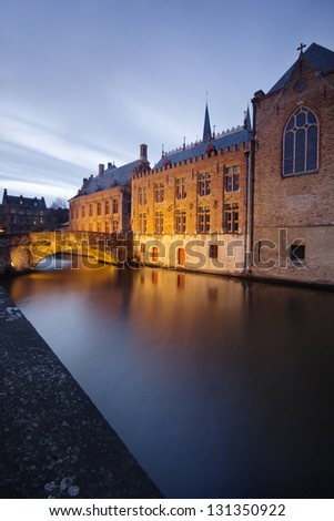 Beautiful old houses and a bridge reflected in the charismatic canals from Bruges (Brugge) - Belgium.