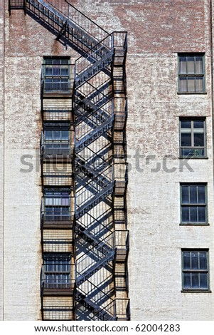 Beautiful old metal fire escape with shadows on brick building - stock photo