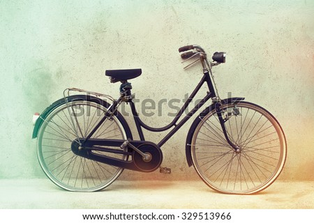 beautiful Old rusty bicycle retro with awesome effect colors on grunge grey background outodoors.