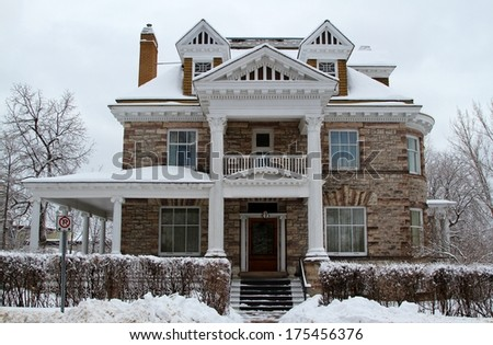 Beautiful old stone three storey mansion in winter - stock photo