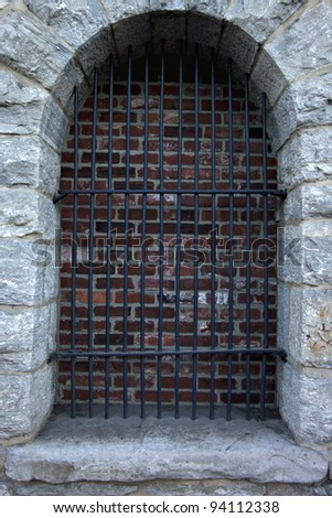 Beautiful old stone window or door with security bars and interior brick showing - stock photo